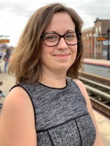 woman with brown hair glasses, grey dress standing in city