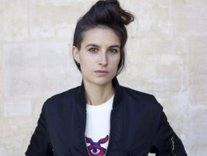 marion with brown hair in top knot wearing white tee and black bomber jacket