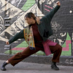 A dancer strikes a dramatic pose on the street