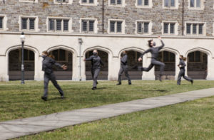 masked dancers in grassy courtyard by arched stone walls