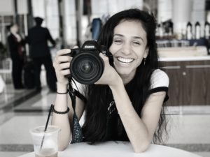 danica smiles with long dark hair, holds camera
