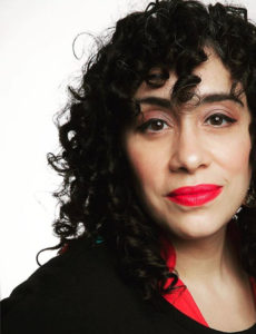 larissa with black curly hair and birght red lips